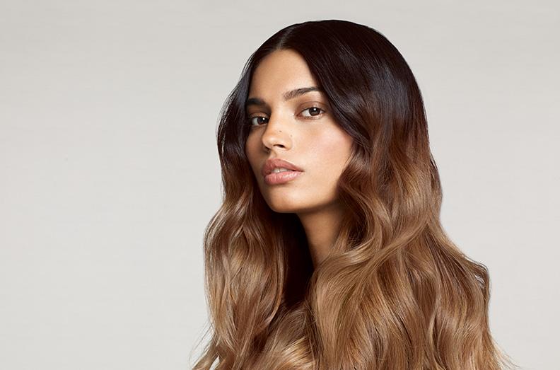 Una mujer con un hermoso cabello de las raíces a las puntas después de un tratamiento de cabello y cuero cabelludo