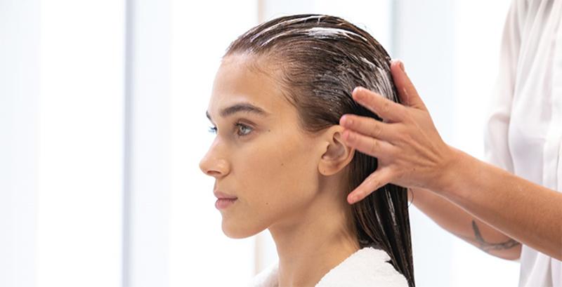 Una mujer recibiendo un tratamiento para el cabello y el cuero cabelludo