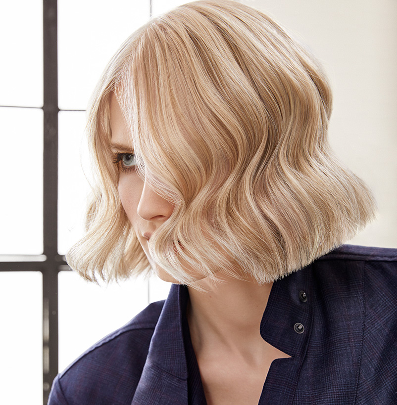A woman with a bob cut and light blond hair color
