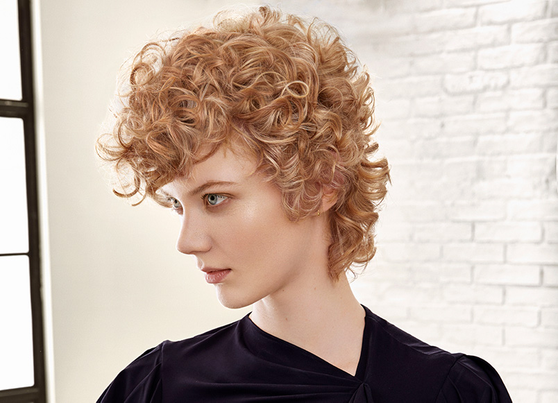 A woman with a modern mullet and golden blond hair color